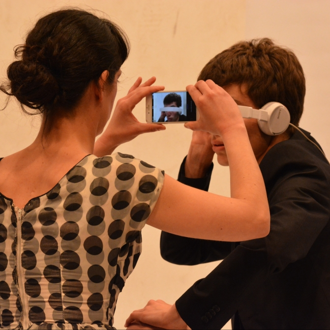 A man wearing a black suit and headphones as they were glasses is recorded with an iPhone by a woman wearing a white dress with black dots.